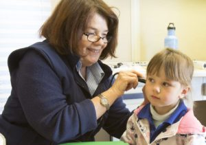 Young client undergoing a hearing test during Healthy Bus Stop visit