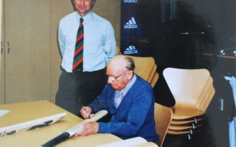 Sir Donald Bradman signing cricket bat