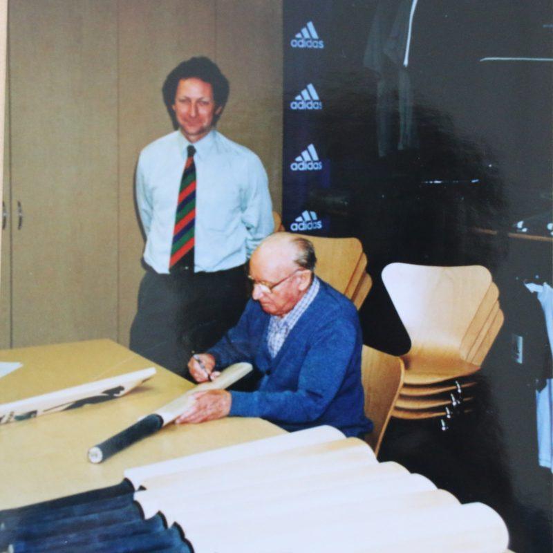 Sir Donald Bradman signing cricket bat