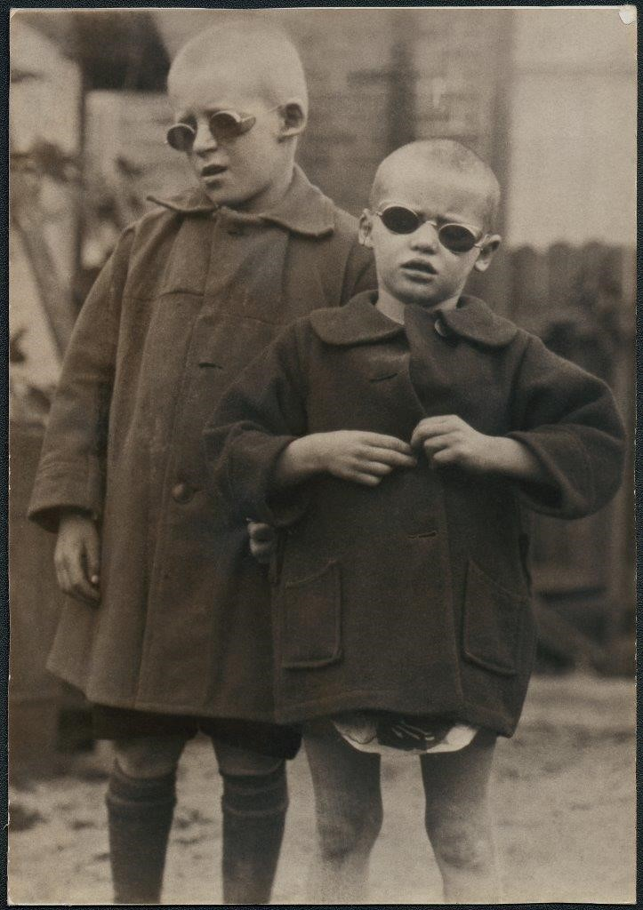 Brother and sister Teddy and Grace, suffering from sandy blight (trachoma), wearing new tinted, corrective spectacles, 1928.
